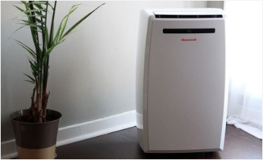 A picture of a small portable Honeywell air conditioner sitting on the floor in the corner of the room.