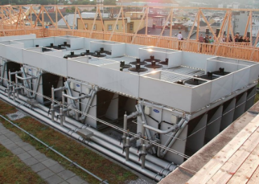 A picture of a major HVAC installation project taken from the second floor of construction. Several grouped unites are put in place with surrounding wood frames built up around it.
