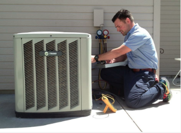 Photo of a technician completing a routine maintenance check up on a residential exterior AC unit.